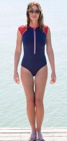 Carole Radziwill in swimsuit strolling on the beach